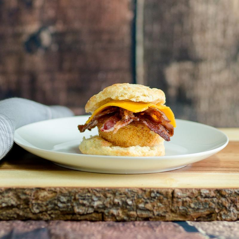 A tall breakfast sandwich with loads of bacon sits on a white plate on a wooden board.