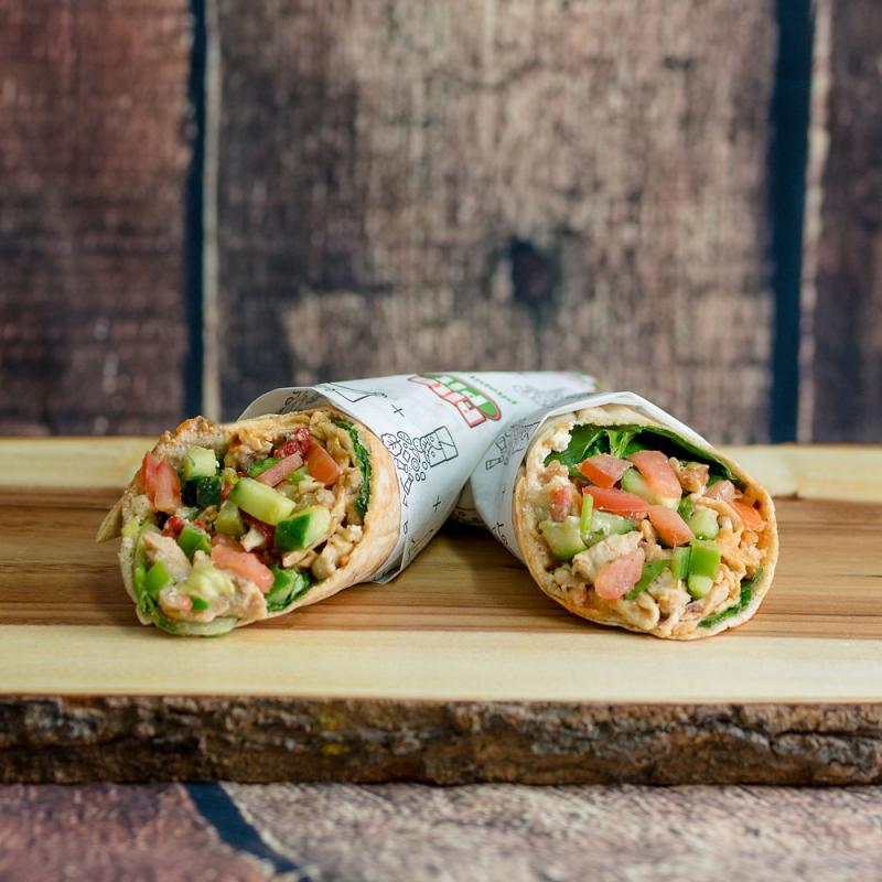 A tightly wrapped burrito is cut into two with bright veggies and seasoned chicken on top of a wooden board.